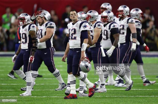 Tom Brady of the New England Patriots walks off the field with teammates after a fumble in the second quarter against the Atlanta Falcons during...