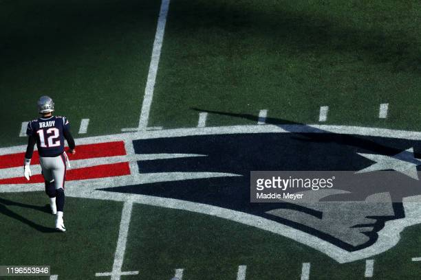 Tom Brady of the New England Patriots walks over the Patriots logo during the game against the Miami Dolphins at Gillette Stadium on December 29 2019...
