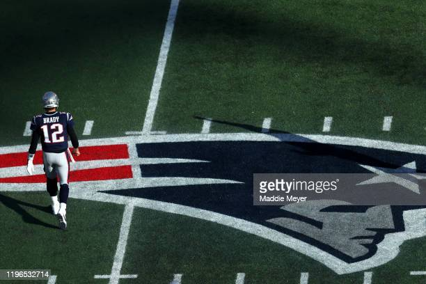 Tom Brady of the New England Patriots walks to the bench over the Patriots logo during the game against the Miami Dolphins at Gillette Stadium on...