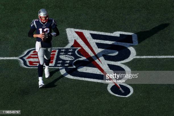 Tom Brady of the New England Patriots warms up over the NFL 100 logo before the game against the Miami Dolphins at Gillette Stadium on December 29...