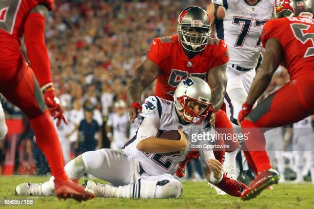 Tom Brady of the Patriots slides short of the goal line as Clinton McDonald of the Bucs closes in during the NFL Regular game between the New England...