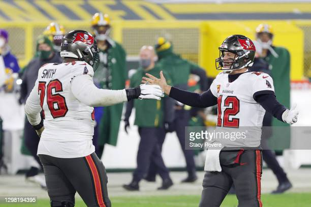 Tom Brady of the Tampa Bay Buccaneers celebrates their 31 to 26 win over the Green Bay Packers with teammate Donovan Smith during the NFC...