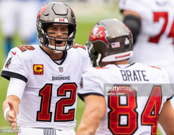 Tom Brady of the Tampa Bay Buccaneers celebrates with teammate Cameron Brate after scoring a touchdown during the first quarter of a game against the...