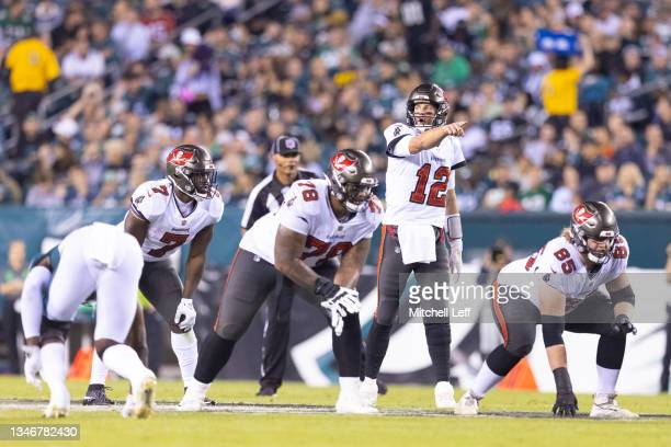Tom Brady of the Tampa Bay Buccaneers points as Leonard Fournette, Tristan Wirfs, and Alex Cappa look on against the Philadelphia Eagles at Lincoln...