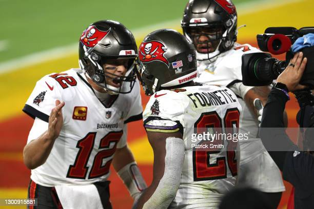 Tom Brady of the Tampa Bay Buccaneers reacts with Leonard Fournette after a 27 yard touchdown run by Fournette in the third quarter against the...