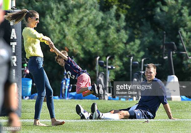 Tom Brady sits while his wife Gisele Bundhen spins their son Benjamin as the New England Patriots end their last practice on Thursday August 15...