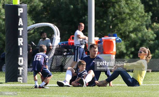 Tom Brady sits with wife Gisele Bundhen and their sons Benjamin center and Jack as the New England Patriots end their last practice on Thursday...