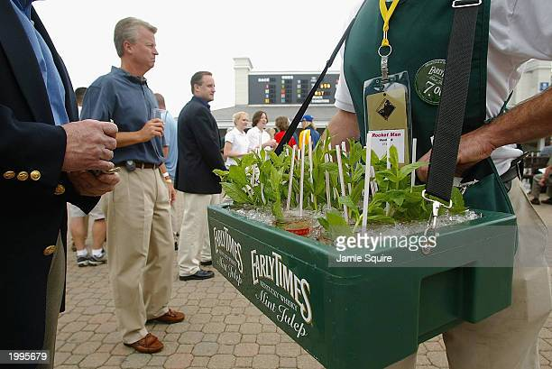 Tom Brisgone buys a Mint Julep from Rudi Keller prior to the 129th Kentucky Oaks on May 2 2003 at Churchill Downs in Louisville Kentucky