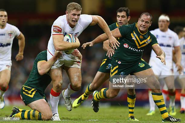 Tom Burgess of England cuts between Luke Lewis and Matthew Scott of Australia during the Rugby League World Cup Group A match between Australia and...
