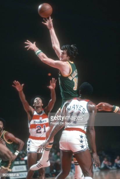 Tom Burleson of the Seattle Supersonics shoots over Dave Bing and Elvin Hayes of the Washington Bullets during an NBA basketball game circa 1975 at...