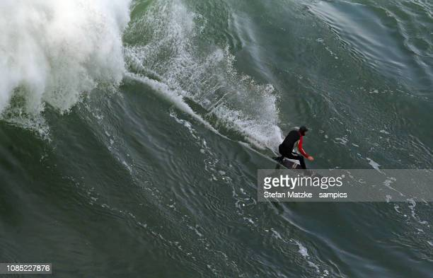 Tom Butler of Great Britain rides a big wave on December 10 2018 in Nazare Portugal