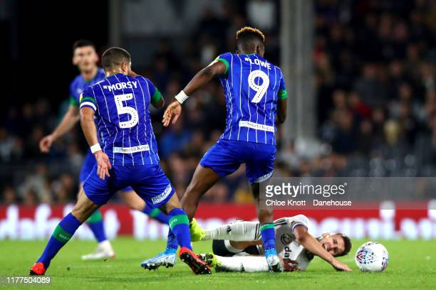 Tom Cairney of Fulham FC get tackled by Sam Sayed Morsy and Jamal Lowe of Wigan Athletic during the Sky Bet Championship match between Fulham and...
