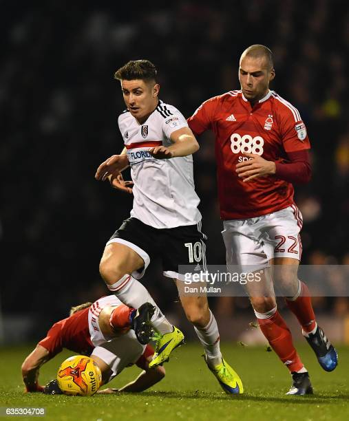 Tom Cairney of Fulham holds off Ben Osborn and Pajtim Kasami of Nottingham Forest during the Sky Bet Championship match between Fulham and Nottingham...