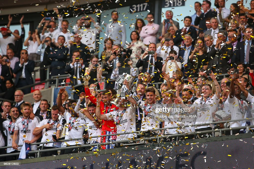 Tom Cairney of Fulham lifts the Sky Bet Championship play off trophy with his team mates during the Sky Bet Championship Play Off Final between Aston Villa and Fulham at Wembley Stadium on May 26, 2018 in London, England.