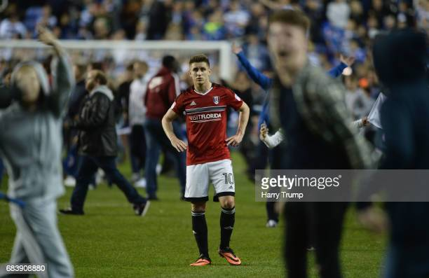 Tom Cairney of Fulham looks dejected as Reading fans invade the pitch in celebration after the Sky Bet Championship Play Off Second Leg match between...
