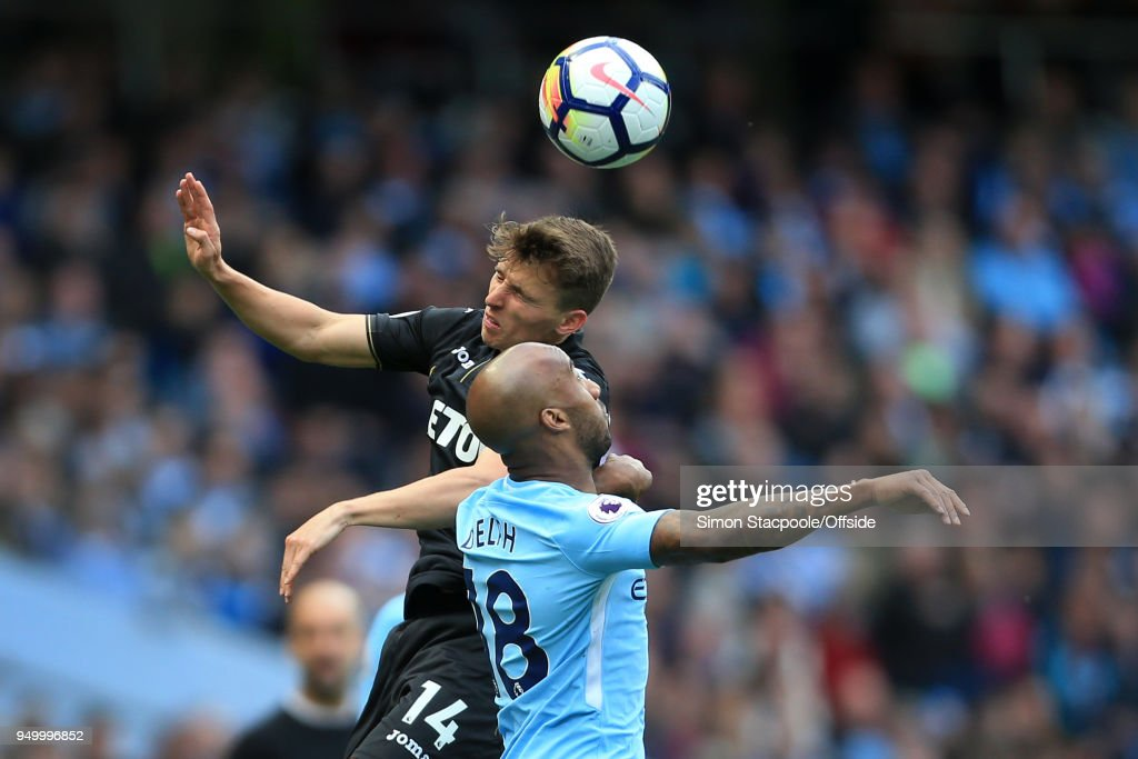 Tom Carroll of Swansea battles with Fabian Delph of Man City during the Premier League match between Manchester City and Swansea City at the Etihad Stadium on April 22, 2018 in Manchester, England.
