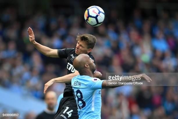 Tom Carroll of Swansea battles with Fabian Delph of Man City during the Premier League match between Manchester City and Swansea City at the Etihad...
