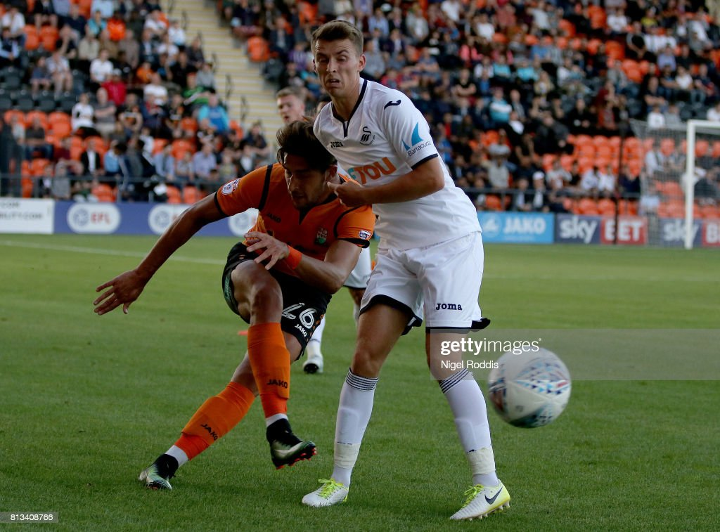 Tom Carroll of Swansea (R) challenges Dan Sweeney of Barnet during the pre season friendly match between Barnet and Swansea City at The Hive on July 12, 2017 in Barnet, England.