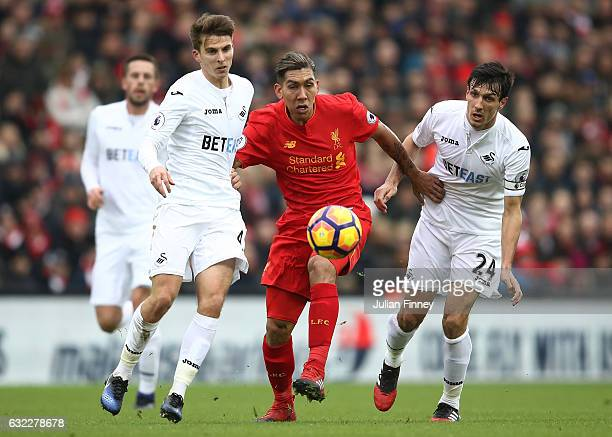 Tom Carroll of Swansea City and Jack Cork of Swansea City attempt to tackle Roberto Firmino of Liverpool during the Premier League match between...