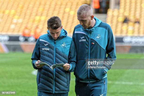 Tom Carroll of Swansea City and team mate Oliver McBurnie read the match program during the Emirates FA Cup match between Wolverhampton Wanderers and...