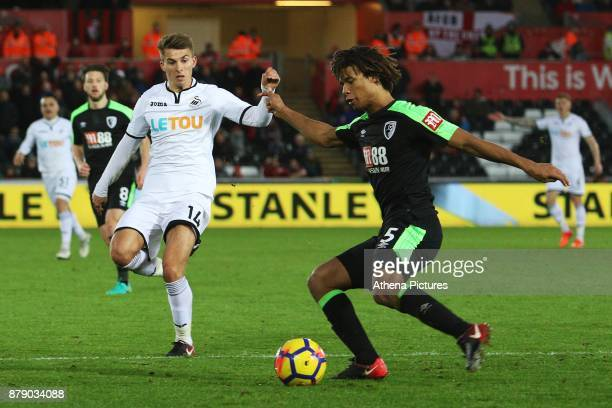 Tom Carroll of Swansea City challenges Nathan Ake of Bournemouth during the Premier League match between Swansea City and Bournemouth at the Liberty...