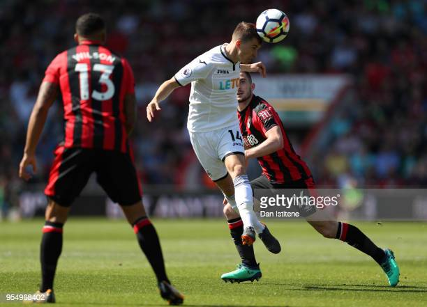 Tom Carroll of Swansea City heads the ball as Lewis Cook of AFC Bournemouth and Callum Wilson of AFC Bournemouth looks on during the Premier League...