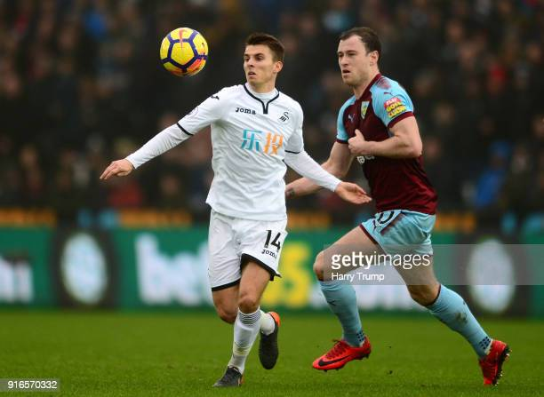 Tom Carroll of Swansea City is challenged by Ashley Barnes of Burnley during the Premier League match between Swansea City and Burnley at Liberty...