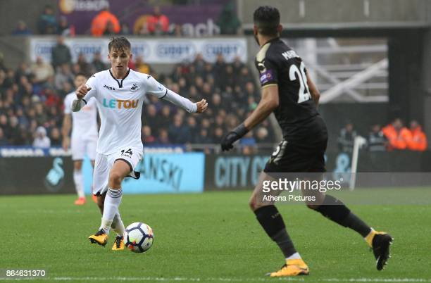 Tom Carroll of Swansea City is marked by Riyad Mahrez of Leicester City during the Premier League match between Swansea City and Leicester City at...