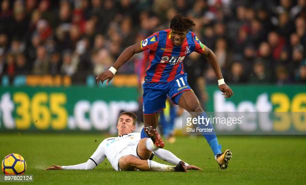Tom Carroll of Swansea City tackles Wilfried Zaha of Crystal Palace during the Premier League match between Swansea City and Crystal Palace at...