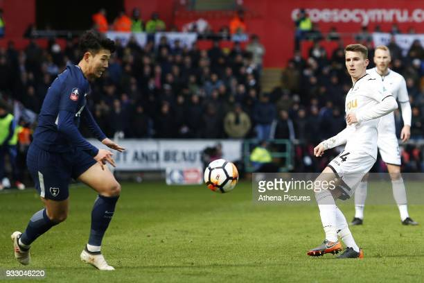 Tom Carroll of Swansea threads a through ball down the win as Son Heungmin of Tottenham Hotspur watches during the Fly Emirates FA Cup Quarter Final...