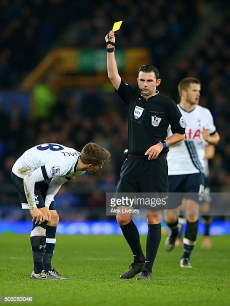 Tom Carroll of Tottenham Hotspur receives a yellow card from referee Michael Oliver during the Barclays Premier League match between Everton and...