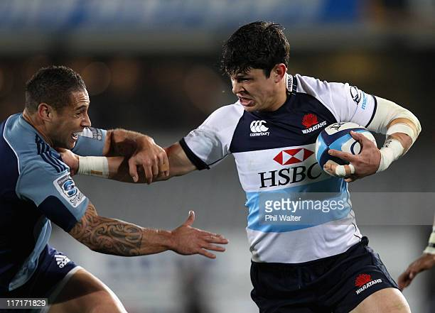 Tom Carter of the Waratahs fends off Luke McAlister of the Blues to score a try during the Super Rugby qualifier match between the Blues and the...