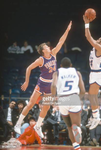 Tom Chambers of the Phoenix Suns leaps to defend the shot of Jeff Malone of the Washington Bullets during an NBA basketball game circa 1990 at the...