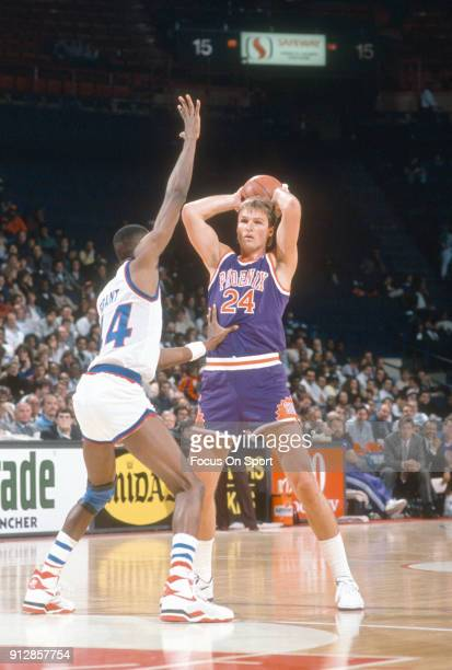 Tom Chambers of the Phoenix Suns looks to pass the ball over the top of Harvey Grant of the Washington Bullets during an NBA basketball game circa...