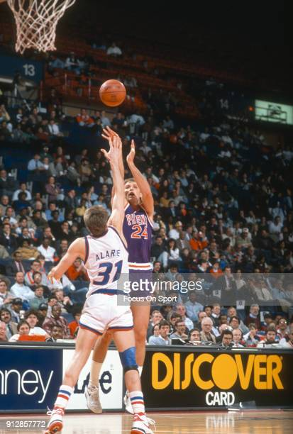 Tom Chambers of the Phoenix Suns shoots over Mark Alarie of the Washington Bullets during an NBA basketball game circa 1990 at the Capital Centre in...