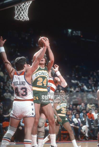 Tom Chambers of the Seattle Supersonics looks to shoot over Jeff Ruland of the Washington Bullets during an NBA basketball game circa 1984 at the...
