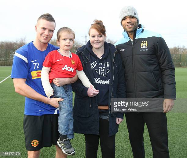 Tom Cleverley of Manchester United and Joleon Lescott of Manchester City pose with Cailin Van Straaten 18 and her brother Zak Jones who were rescued...