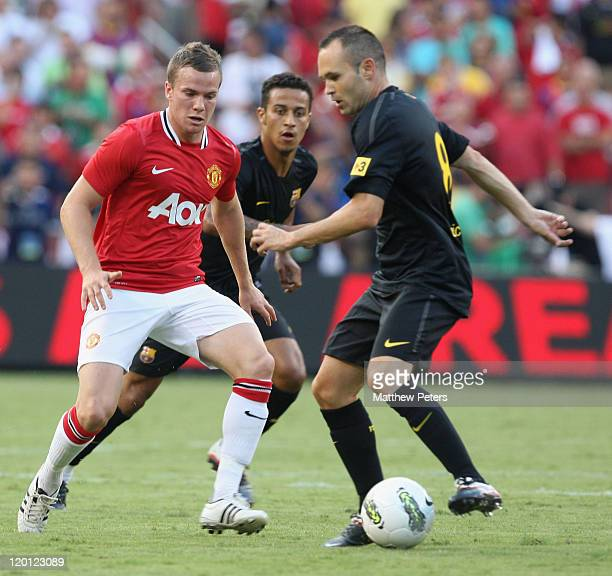 Tom Cleverley of Manchester United clashes with Andres Iniesta of Barcelona during the pre-season friendly match between Manchester United and...