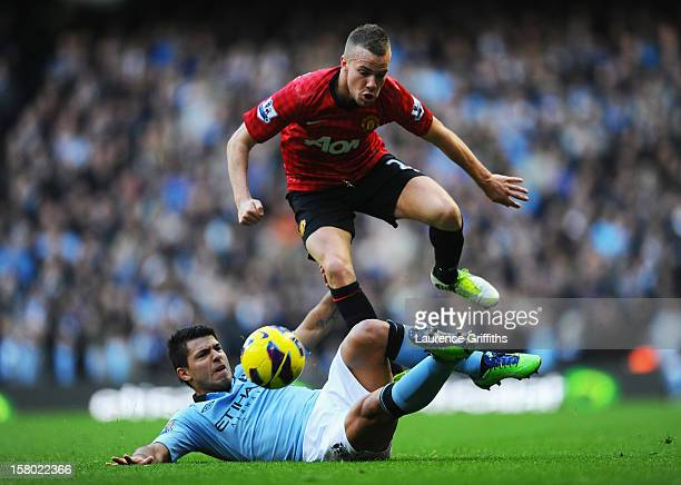 Tom Cleverley of Manchester United hurdles the tackle of Sergio Aguero of Manchester City during the Barclays Premier League match between Manchester...