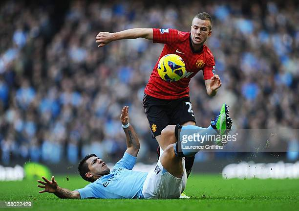 Tom Cleverley of Manchester United is challenged by Sergio Aguero of Manchester City during the Barclays Premier League match between Manchester City...