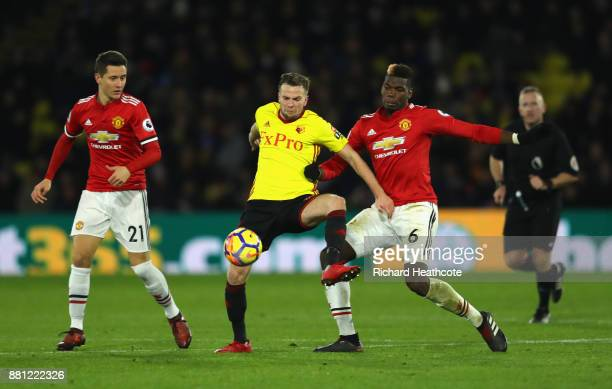 Tom Cleverley of Watford is tackled by Paul Pogba of Manchester United as Ander Herrera looks on during the Premier League match between Watford and...
