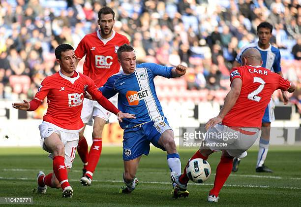 Tom Cleverley of Wigan is tackled by Stephen Carr of Birmingham during the Barclays Premier League match between Wigan Athletic and Birmingham City...