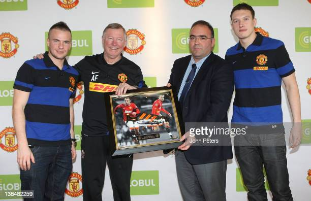 Tom Cleverly Sir Alex Ferguson and Phil Jones of Manchester United present a signed Dimitar Berbatov boot to Haris Kotsibos CEO of Globul after a...