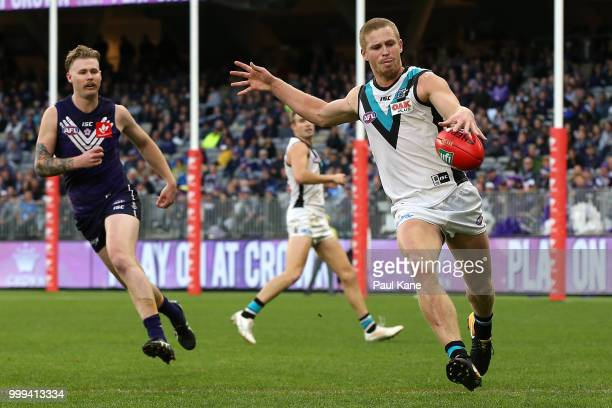 Tom Clurey of the Power passes the ball during the round 17 AFL match between the Fremantle Dockers and the Port Adelaide Power at Optus Stadium on...