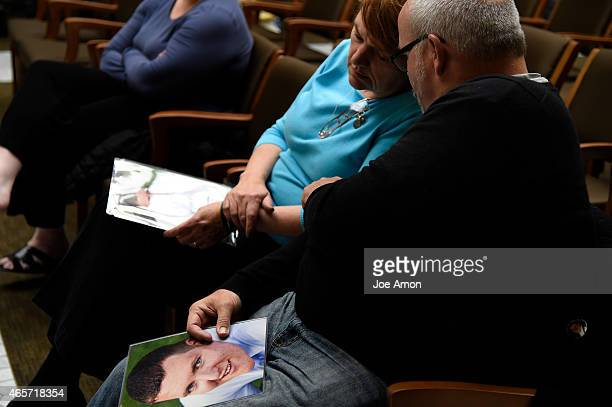 Tom comforts his wife Terry Sullivan after testifying with a photo of their son Alex Sullivan who died during the theater shooting's in Aurora...