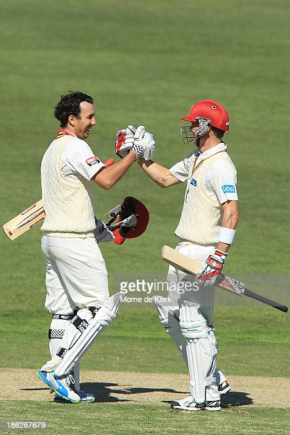 Tom Cooper and Johan Botha of the Redbacks celebrates after Cooper made 100 runs during day one of the Sheffield Shield match between the South...
