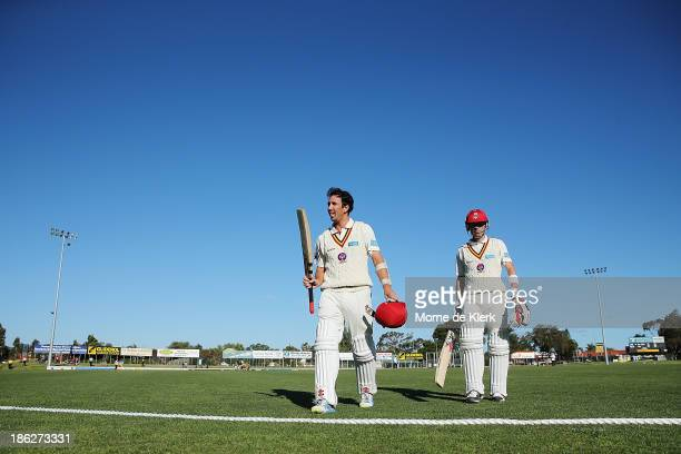Tom Cooper and Johan Botha of the Redbacks leave the field after day one of the Sheffield Shield match between the South Australia Redbacks and the...