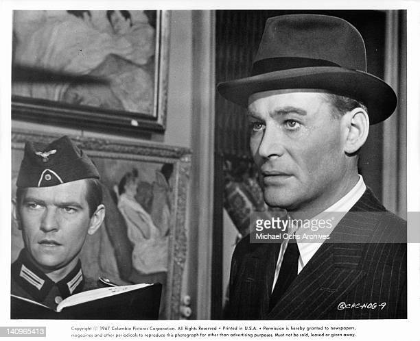 Tom Courtenay and Peter O'Toole stand and stare in the same direction in a scene from the film 'Night Of The Generals', 1966.