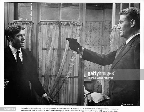 Tom Courtenay stands as Peter O'Toole points a gun at him in a scene from the film 'Night Of The Generals', 1966.
