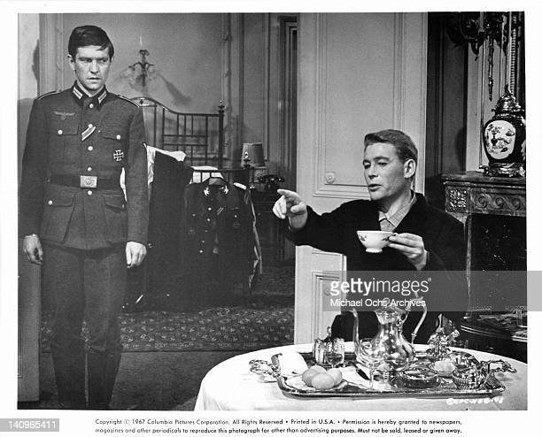Tom Courtenay stands as Peter O'Toole points his finger forward in a scene from the film 'Night Of The Generals', 1966.